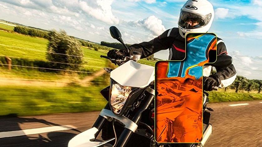 Motorradfahrer, der eine Kühlweste trägt. Er fährt scheinbar schnell über eine Landstrasse. Der Hintergrund ist unscharf