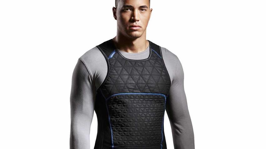 Sportler, welcher eine schwarte Kühlweste über seinen grauen Trainingsanzug trägt
