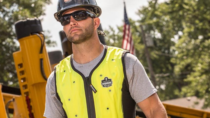 Bauarbeiter trägt eine Kühlweste. Die Weste ist Signal-gelb. Im Hintergrund sieht man maschienen